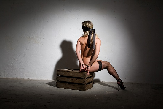 bondage date - girl blindfolded with a silk scarf and bound in a dungeon with handcuffs