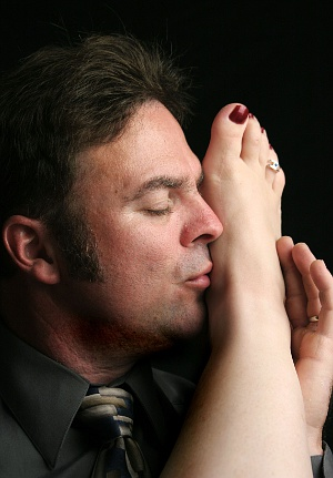 handsome man kissing a woman's foot